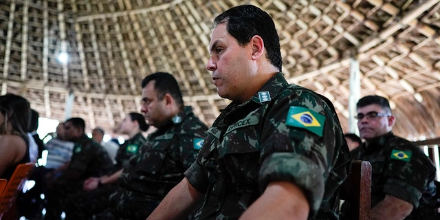 Military officers listen to the testimony of Temehe Tomas Waimiri about alleged crimes committed by Brazil's dictatorship in the 1970s during a hearing on the Waimiri-Atroari reserve, in Brazil's Amazon state, Wednesday, Feb. 27, 2019. Now elderly, indigenous men described horrific scenes that put a spotlight on Brazil's military, which denies attacking the tribe. (AP Photo/Victor R. Caivano)
