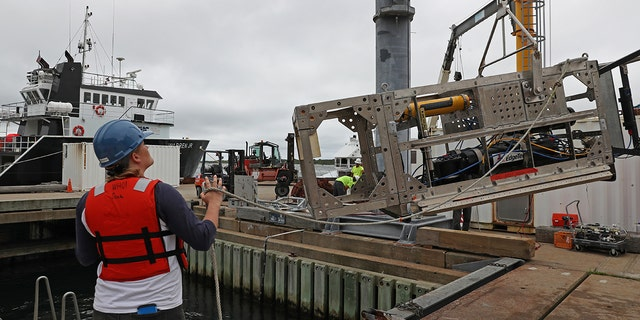 Kaitlyn Tradd, a mechanical engineer at Woods Hole Oceanographic Institution, looks on as a crane lifts one of the new instruments, a $1.2 million, 2,500-pound, specially designed system of sonars and cameras called DEEP-SEE. (Photo by David L. Ryan/The Boston Globe via Getty Images)