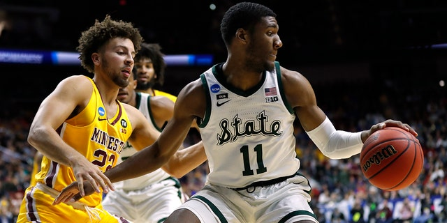 Michigan State forward Aaron Henry (11) drives around Minnesota guard Gabe Kalscheur. (Associated Press)