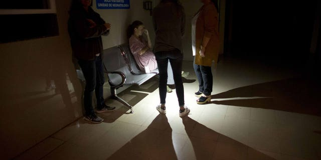Mothers and relatives wait outside of an intensive care room for babies at a clinic, during a power outage in Caracas, Venezuela, Thursday, March 7, 2019. A power outage left much of Venezuela in the dark early Thursday evening in what appeared to be one of the largest blackouts yet in a country where power failures have become increasingly common.