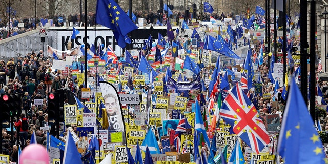 Demonstrators carry posters and flags during a Peoples Vote anti-Brexit march in London, Saturday.