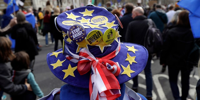 A demonstrator wears a hat decorated with the EU and British colors during a Peoples Vote anti-Brexit march in London, Saturday.