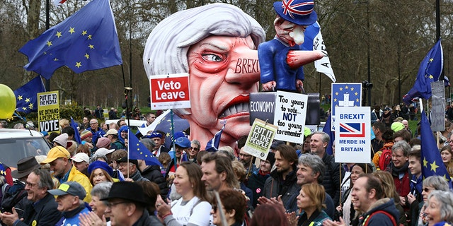 A puppet character depicting Prime Minister Theresa May is brandished among Anti -Brexit campaigners, during the People's Vote March in London, Saturday March 23, 2019. Protesters are gathering in central London before going on a massive march in favor of a second Brexit referendum. (Yui Mok / PA via AP)