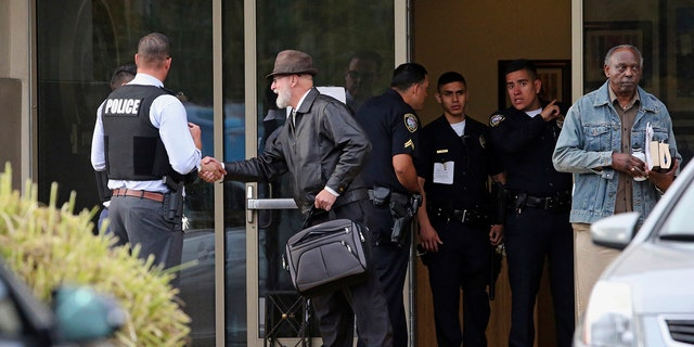An unidentified man who had been inside the building shakes officers' hands outside the Church of Scientology in Inglewood, Calif., on Wednesday. (Associated Press)