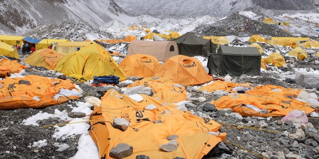 In this photograph taken on April 26, 2015, rocks are kept over flattened tents at Everest Base Camp, to cover the bodies of some of the people that died a day earlier as an earthquake triggered avalanche crashed through parts of the base camp killing scores of people.