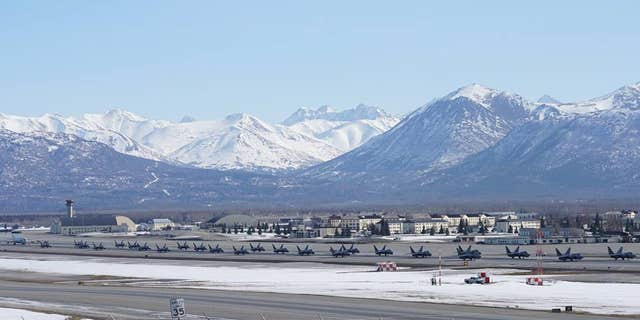 24 F-22 Raptors, a C-17 Globemaster III and an E-3 Sentry gathered on the Joint Base Elmendorf-Richardson flight line.