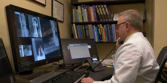 Dr. Sauerwine Scott examines X-rays of the Peruvian mummy.