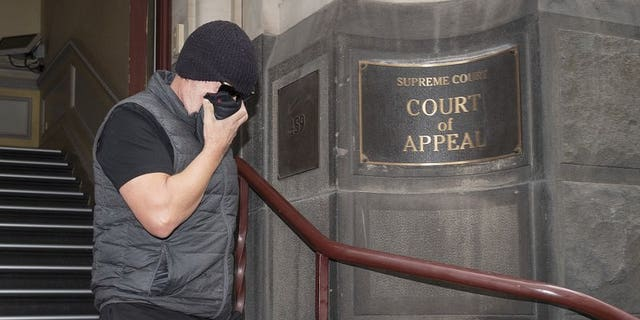Workplace bullying claimant David Hingst covers his face as he leaves the Court of Appeal in Melbourne, Australia Friday, March 29, 2019. The Australian appeals court on Friday dismissed a bullying case brought by the engineer Hingst who accused his former supervisor of repeatedly breaking wind toward him.