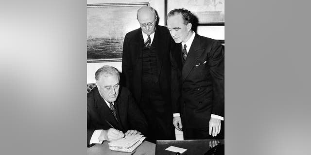 FILE - In this Jan. 2, 1939, file photo, the old family Bible Frank Murphy used in taking his oath of office in the president's study in the White House is autographed by President Franklin Roosevelt immediately after ceremony. Watching are Homer Cummings, center, retiring attorney general, and Murphy, right, the new attorney general. Presidents have a long history of signing Bibles, though earlier presidents typically signed them as gifts to send with a spiritual message. (AP Photo, File)