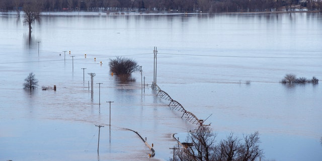 Looking southwest toward Waterloo, Neb., high waters from the Elkhorn River cover Maple Street on Saturday. (Jeff Bundy/Omaha World-Herald via AP)