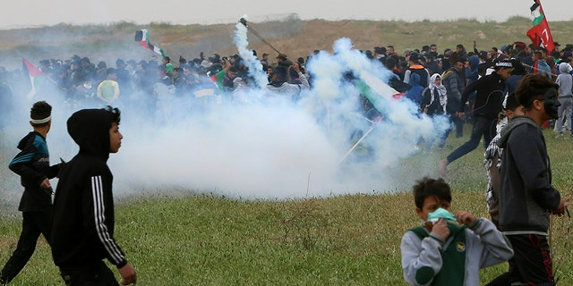 Demonstrators run for tear gas fired by Israeli troops near the border fence to Gaza with Israel, and celebrate the first anniversary of the Gaza border protests east of Gaza on Saturday, March 30, 2019 (AP Photo / Adel Hana)