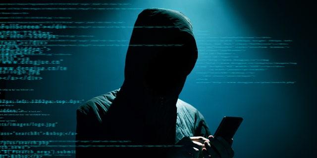 Hacker Hacker using phone at dark (Credit: iStock)