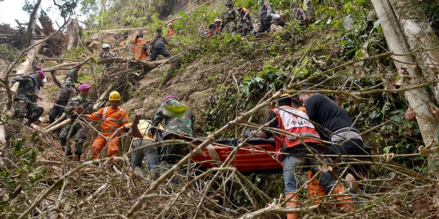Rescuers carry a survivor of the collapsed mine on a stretcher through a steep terrain.