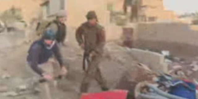 A Fox News team in Syria can see terroristsscavenging, milling around closely. Sometimes they shout. They're moving around, driving motorbikes, digging for roots, and carrying AK47s and RPGs.