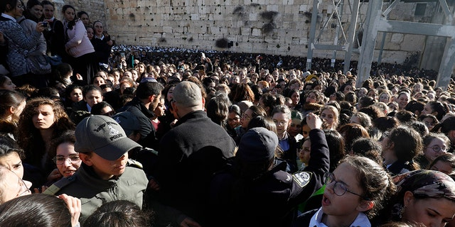 """Thousands of Ultra Orthodox Jewish girls gather at Judaism's holiest prayer site of the Western Wall in the Old City of Jerusalem on March 8, 2019, in protest against members of the liberal Jewish religious movement """"Women of the Wall"""" (WOW) praying at the site during an event marking the organization's 30th anniversary and the start of the Jewish month (Rosh Hodesh) of Adar Bet."""