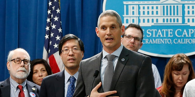 Dr. Eric Ball, center, representing the American Academy of Pediatrics in California, speaks in support of a proposed measure to have public health officials grant medical exemptions for vaccination instead of leaving the power to physicians, during a news conference in Sacramento, Calif.