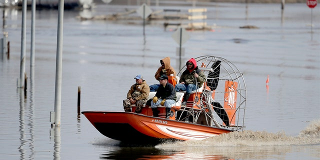 Gabe Schmidt, owner of Liquid Trucking, back right, travels by air boat with Glenn Wyles, top left, Mitch Snyder, bottom right, and Juan Jacobo, bottom left, as they survey damage from the flood waters of the Platte River, in Plattsmouth, Neb., on Sunday.