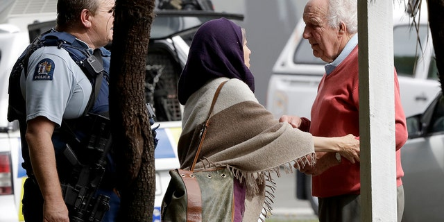 Police escort people away from outside a mosque in central Christchurch, New Zealand, Friday, March 15, 2019. (AP Photo/Mark Baker)