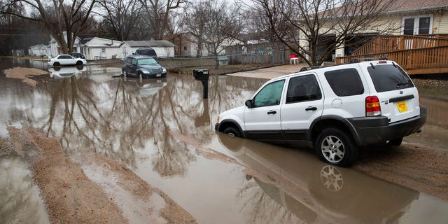 Cars are stuck in floodwaters Tuesday, March 19, 2019, in Fremont, Neb.