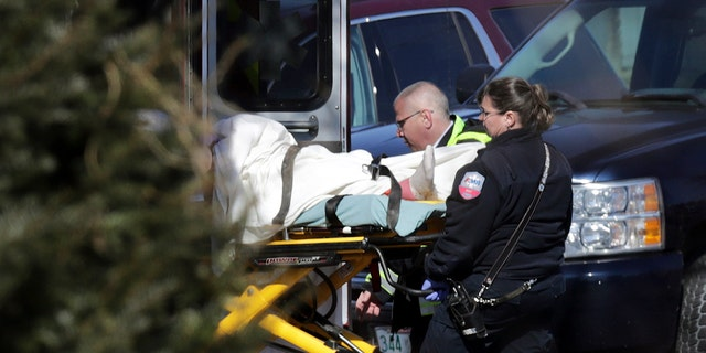 Emergency medical technicians carry a person on a stretcher into an ambulance outside the Quality Inn on Thursday, March 28, 2019, in Manchester, N.H.