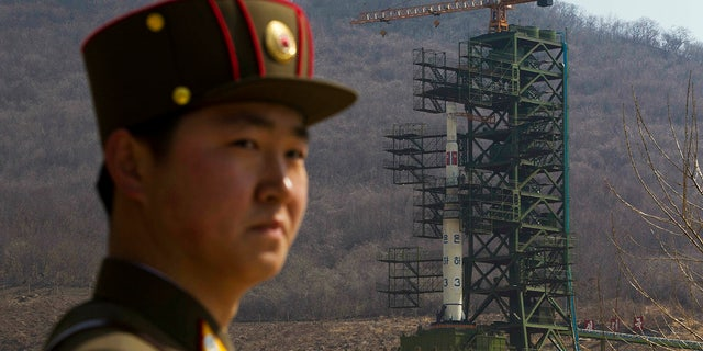 A soldier stands near the Unha-3 rocket at a launching site in Tongchang-ri, North Korea, April 8, 2012. (Associated Press)