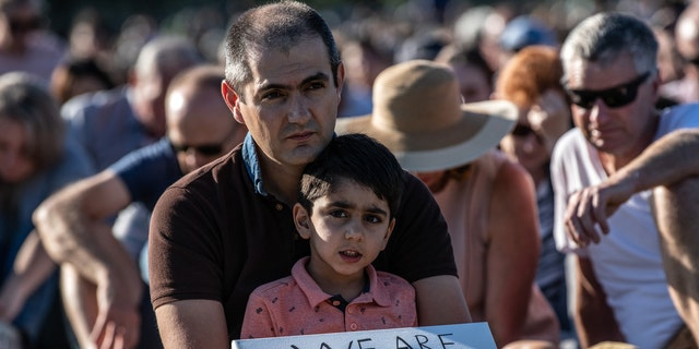 A young boy holds a placard as he takes part in a vigil to remember the victims of the Christchurch mosque attacks
