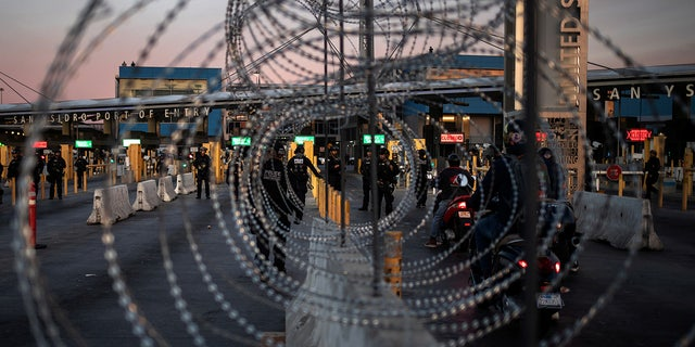 U.S. Customs and Border Protection Special Response Team officers are seen through concertina wire after the San Ysidro Port of Entry land border crossing was temporarily closed to traffic in Tijuana, Mexico in November.