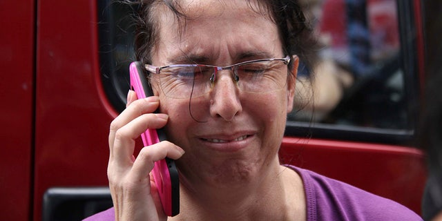 A woman uses her cell phone as she waits for news outside the Raul Brasil State School in Suzano, Sao Paulo state, Brazil.
