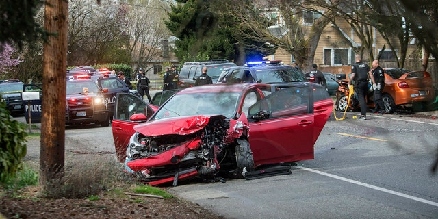 Police are working on the scene as two cars collided in Seattle on Wednesday in Seattle after a firefight on vehicles in a Seattle neighborhood. (Associated Press)