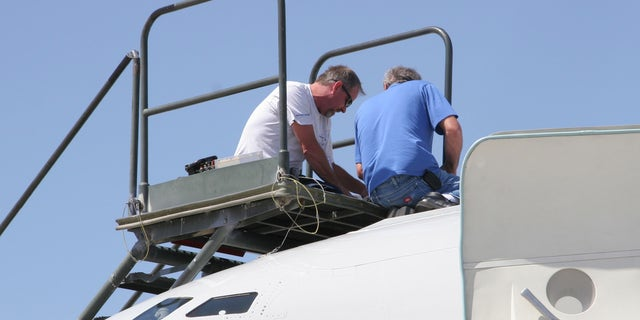 From left, Northrop Grumman technicians Joe McKee and Al Fournier work to repair aerial refueling equipment atop the T-3 test bed version of the E-8C Joint STARS aircraft during Bold Quest at Nellis Air Force Base, Nev., last month. (U.S. Air Force photo)