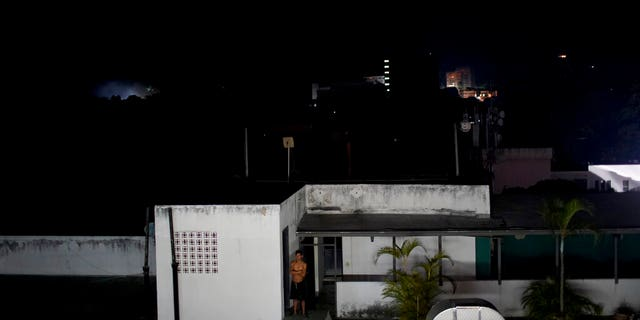 A man stands outside his home during a power outage in Caracas, Venezuela, Monday, March 25, 2019. A new power outage spread across much of Venezuela on Monday, knocking communications offline and stirring fears of a repeat of the chaos almost two weeks ago during the nation's largest-ever blackout.