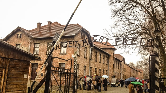 Auschwitz Memorial shares photos of people walking on train track, urges respect