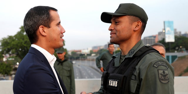 """Venezuelan opposition leader Juan Guaido, who many nations have recognized as the country's rightful interim ruler, shakes hands with a military member near the Generalissimo Francisco de Miranda Airbase """"La Carlota"""", in Caracas, Venezuela April 30, 2019. REUTERS/Carlos Garcia Rawlins - RC197DFD5580"""
