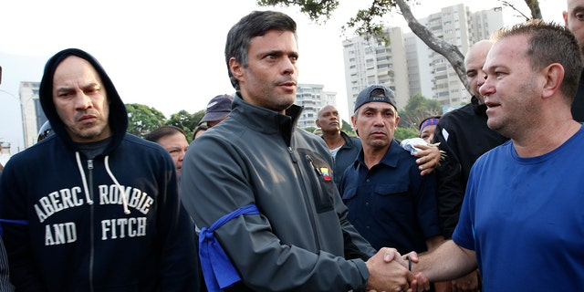 Opposition leader Leopoldo Lopez, center, is greeted by a supporter in Caracas Tuesday. (AP Photo/Ariana Cubillos)