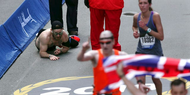Micah Herndon crawls to the finish line in the 123rd Boston Marathon on Monday in Boston.