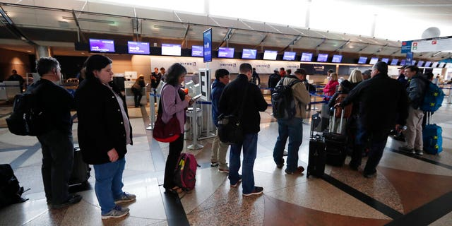 Passengers wait in a line to rebook their flights at the United Airlines counter in Denver International Airport Wednesday, April 10, 2019, in Denver.