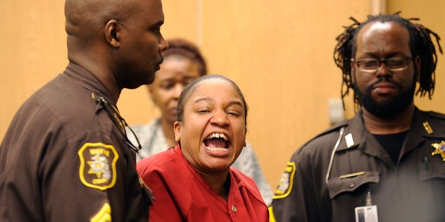 Mitchelle Blair is led out of the courtroom by Wayne County Sheriff deputies after an outburst during a custody hearing before Wayne County Circuit Judge Edward Joseph Thursday, June 4, 2015 in Detroit. She was arrested March 24 after court deputies carrying out an eviction at her apartment found the bodies of her children, Stoni Blair, 13, and Stephen Berry, 9, in a deep freezer.