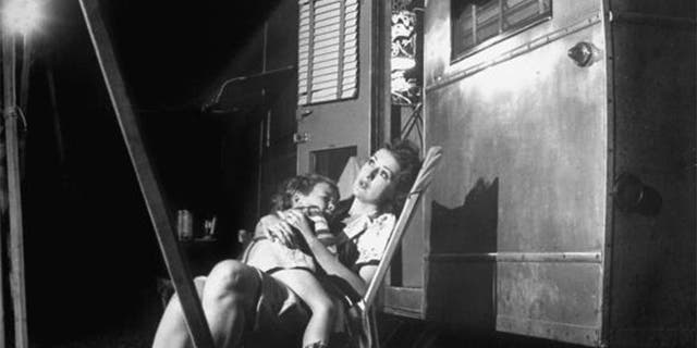 Stripper Gypsy Rose Lee holding her 4-year old son, Erik Lee Kirkland, during a stopover in traveling carnival show.