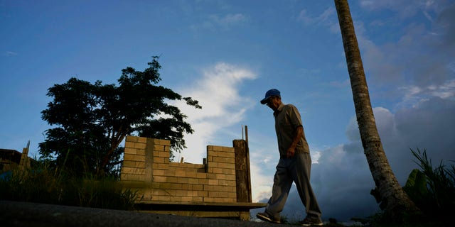 Ramon Alicea Burgos walking past his palm tree, with its top broken off one year earlier by Hurricane Maria outside his partially rebuilt home in Barranquitas, Puerto Rico, in September 2018. (AP Photo/Ramon Espinosa, File)