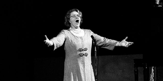 """Kate Smith sings """"God Bless America"""" before an NHL hockey Stanley Cup playoff game between the New York Islanders and the Philadelphia Flyers in Philadelphia in 1975. (Associated Press)"""