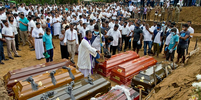 A priest conducts religious rituals during a mass burial for Easter Sunday bomb blast victims in Negombo, Sri Lanka, on Wednesday.