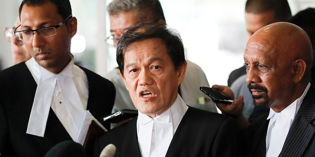 Hisyam Teh Poh Teik, center, and Naran Singh, right, lawyers for Vietnamese Doan Thi Huong speak during a press conference after court hearing at Shah Alam High Court in Shah Alam, Malaysia, Monday, April 1, 2019. (AP Photo/Vincent Thian)