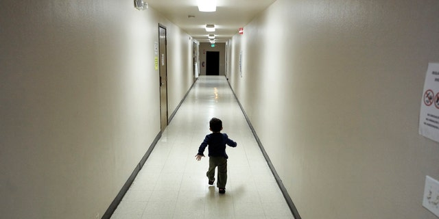 FILE - In this Dec. 11, 2018 file photo, an asylum-seeking boy from Central America runs down a hallway after arriving from an immigration detention center to a shelter in San Diego. San Diego County sued Wednesday, April 3, 2019, to overturn the Trump administration's cancelling of an immigration program that quickly released families after they cross the border without allowing time for travel arrangements. (AP Photo/Gregory Bull, File)
