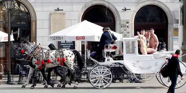 Tourists wearing mankinis travel in a horse cab in Market Square in Krakow, Poland. (AP Photo/Czarek Sokolowski)