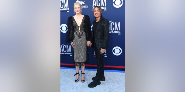 Nicole Kidman, in a shimmery number, and Keith Urban, in an animal print suit, hold hands at the 54th annual Academy of Country Music Awards.