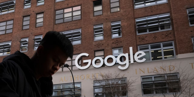 FILE - In this Dec. 17, 2018, file photo, a man using a mobile phone walks past Google offices in New York. Executives from Google and Facebook are facing Congress Tuesday, April 8, 2019, to answer questions about their role in the hate crimes and the rise of white nationalism in the U.S. (AP Photo/Mark Lennihan, File)