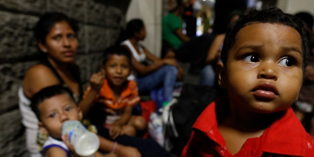 Migrants planning to join a new caravan of several hundred people setting out in hopes of reaching the distant United States, wait at the bus station in San Pedro Sula, Honduras, Tuesday, April 9, 2019. Parents who gathered at the bus station to leave with Wednesday morning's caravan say they can't support their families with what they can earn in Honduras and are seeking better opportunities. (AP Photo/Delmer Martinez)