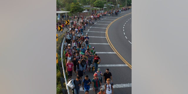 Central American migrants, part of a caravan hoping to reach the U.S. border, walk on the shoulder of a road in Frontera Hidalgo, Mexico on Friday. (Associated Press)
