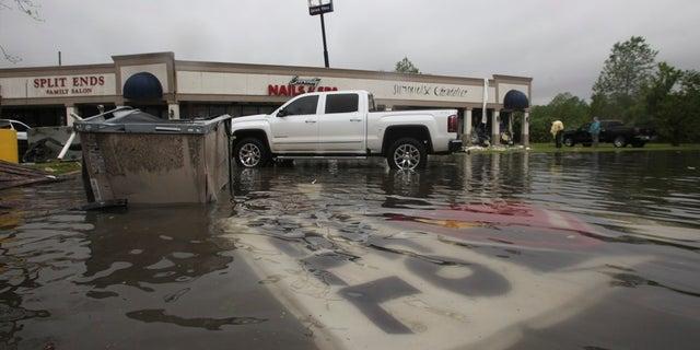 Debris is strewn in flooded water in the Pemberton Quarters strip mall following severe weather Saturday in Vicksburg, Miss. (Associated Press)