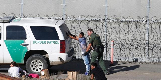 Honduran asylum seekers are taken into custody by U.S. Border Patrol agents in San Diego this past Demceber. (AP Photo/Moises Castillo, File)